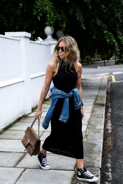 Под черное обтягивающее платье в пол подобрали черные высокие конверсы. Образ дополнили небрежно надетая джинсовая куртка и сумка.