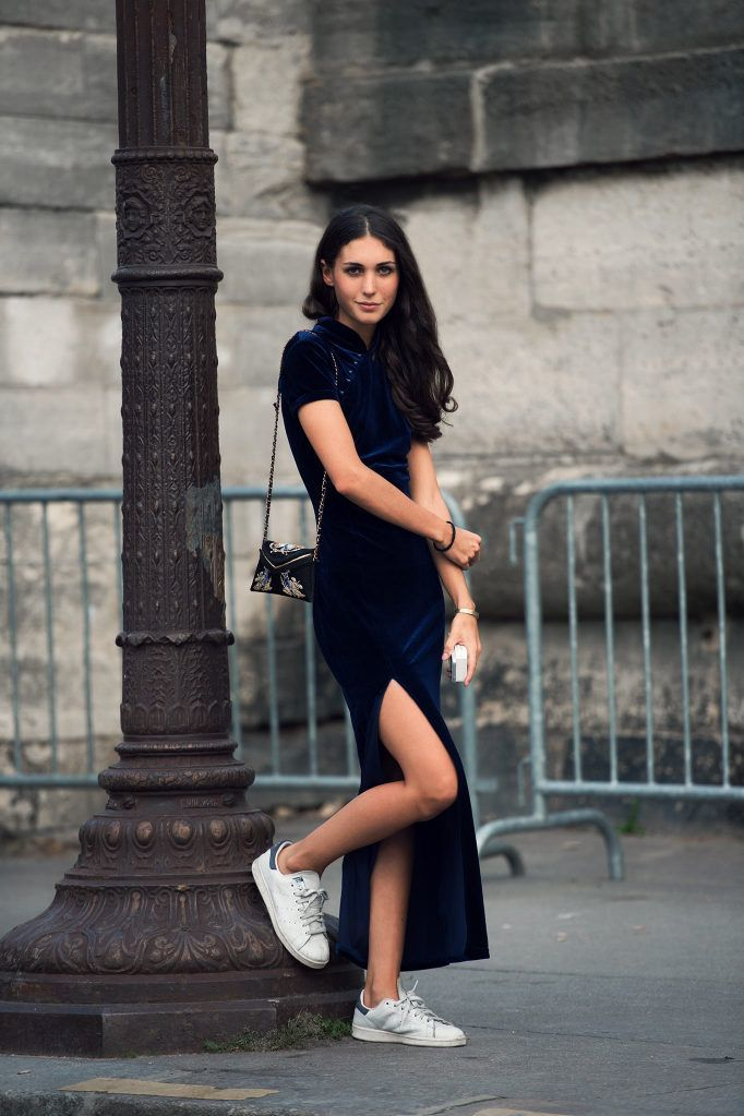 Девушка надела велюровое синее платье с коротким рукавом и простые белые кроссовки, дополнив образ поясной сумкой с вышивкой.