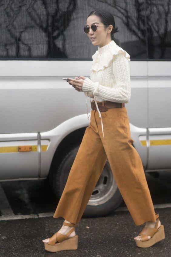 Джинсовые коричневые кюлоты, белый вязаный свитер и кожаные босоножки на танкетке на тон светлее ремня.