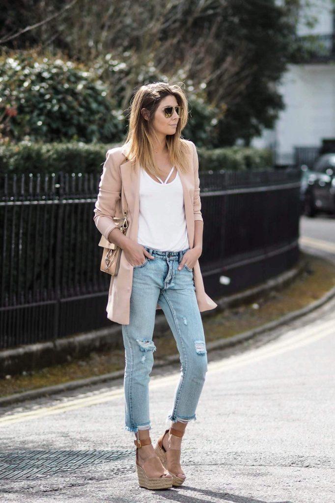 Белая майка, светло-голубые джинсы, нежно-розовый кардиган и нюдовые босоножки на танкетке с ремешками отлично сочетаются вместе.