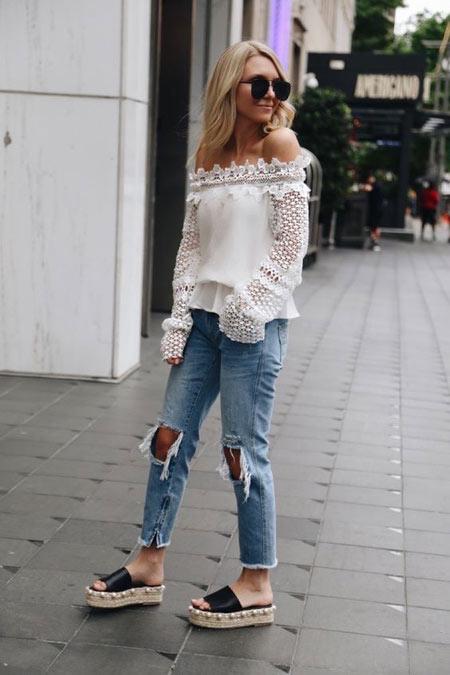 Белая блузка с необычными рукавами, рваные на коленях синие джинсы и босоножки на сплошной платформе.