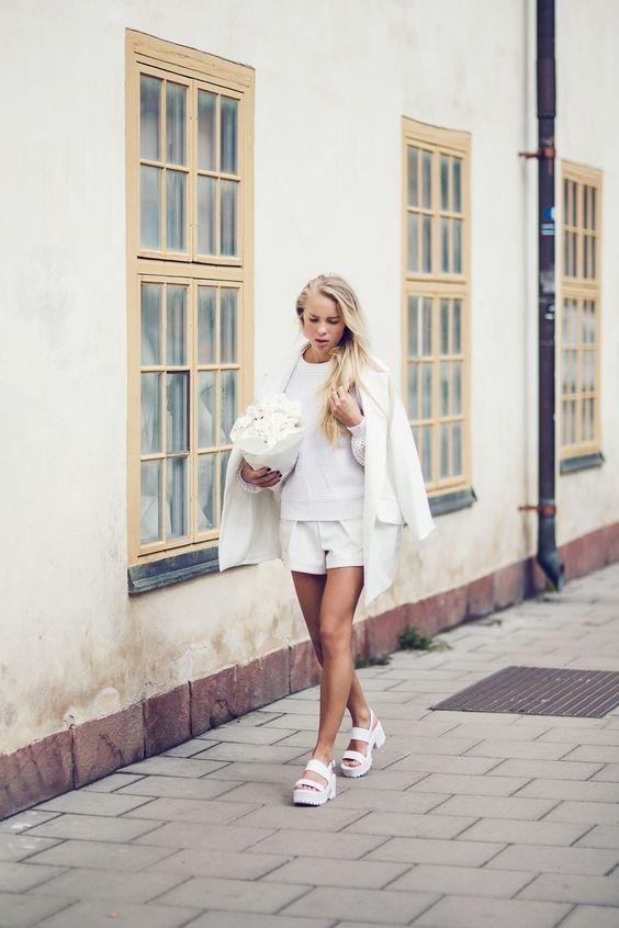 Белый свитер, свободные шорты, кардиган и белые босоножки на платформе отлично сочетаются вместе.