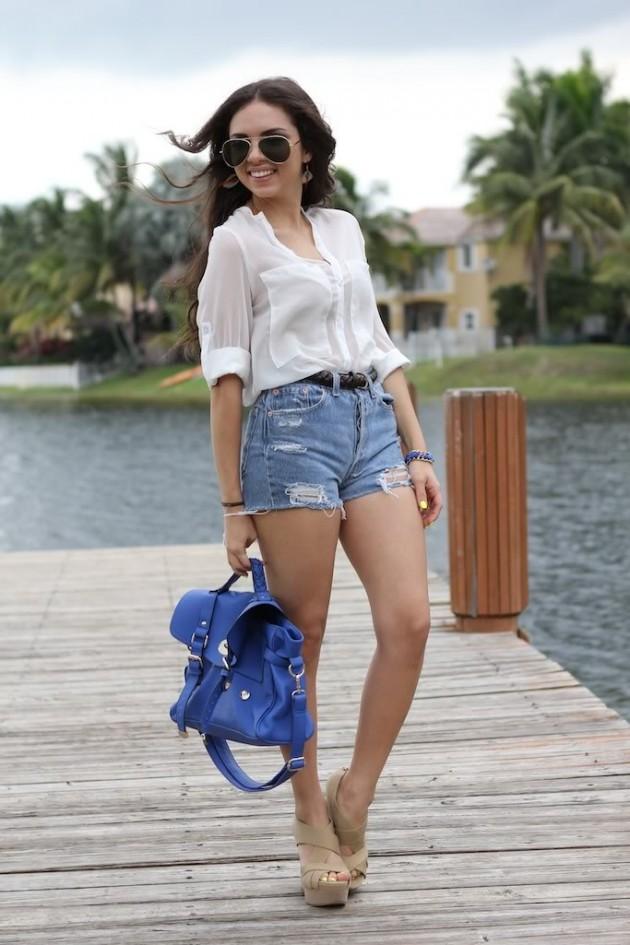 На девушке легкая полупрозрачная белая рубашка, джинсовые голубые шорты и бежевые кожаные босоножки с переплетами.