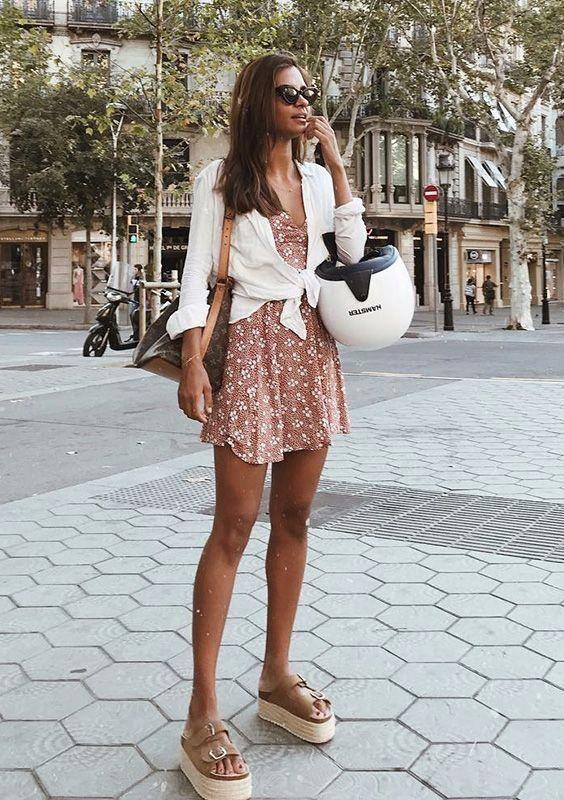 Короткое летнее платье, белая рубашка, завязанная на поясе и коричневые босоножки на высокой сплошной платформе с ремешками. Образ дополняют очки и сумка.