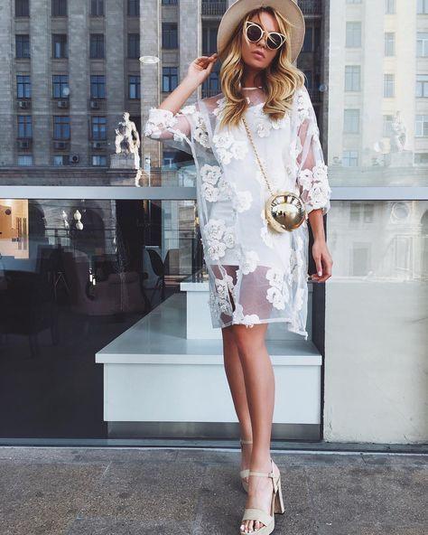 Белое платье с цветами отлично сочетается с бежевыми босоножками на платформе с высоким каблуком и ремешками. Образ дополняют шляпа, очки и маленькая поясная сумка.