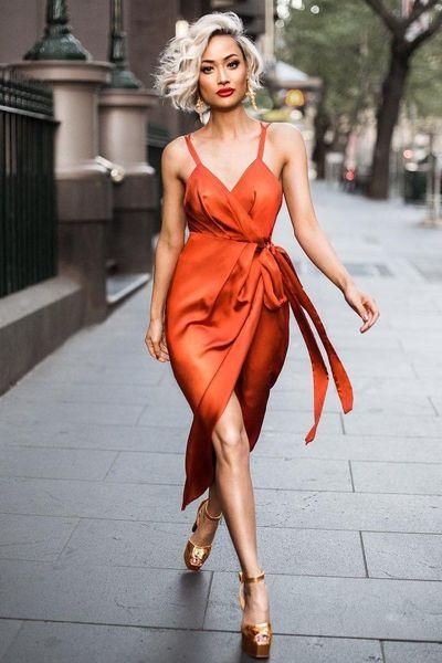 Яркое оранжевое шифоновое платье длины миди с поясом и разрезом сочетается с босоножками на высокой платформе цвета металлик.