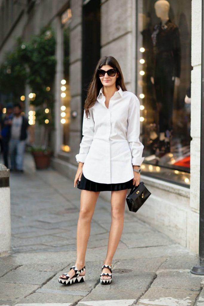 Облегающая белая рубашка отлично выглядит с босоножками на сплошной подошве с геометрическим принтом, лук дополняют очки и кожаная сумка.