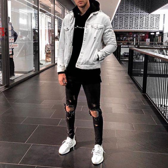 Рваные на коленях черные джинсы отлично смотрятся с белыми кроссовками, худи и светло-голубой джинсовой курткой.