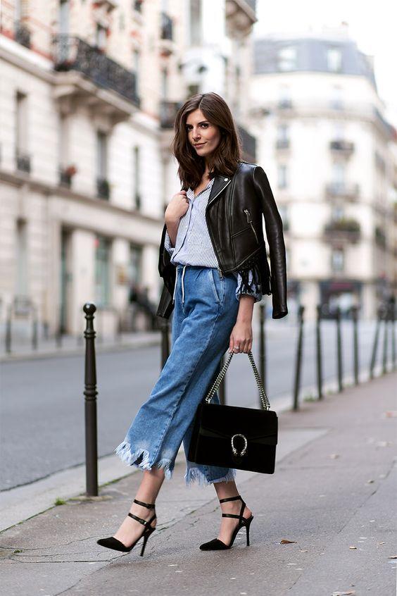 Укороченные джинсы кюлоты, заправленная рубашка и кожаная куртка отлично смотрятся с черными босоножками на высоком каблуке и замшевой сумкой.