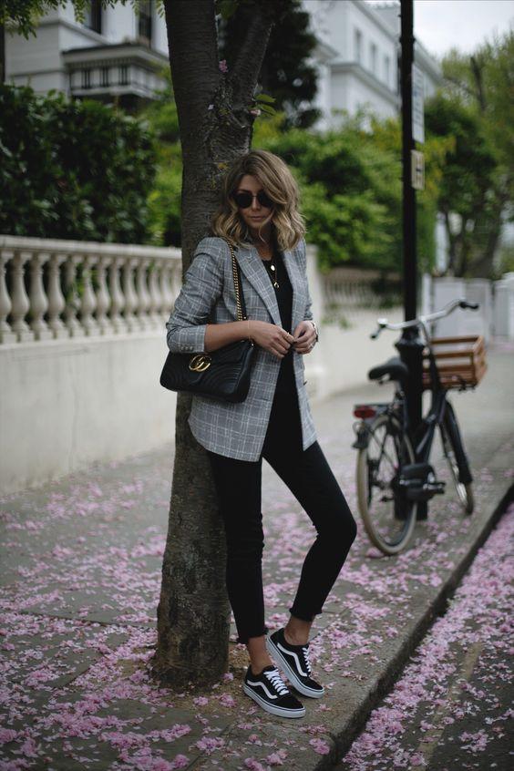 На девушке черные скинни, клетчатый удлиненный серый пиджак и кеды Vans. Образ дополняет кожаная сумка и очки.