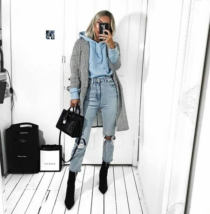 Замшевые черные ботильоны-носки сочетаются с голубыми укороченными джинсами, худи и клетчатым пальто.