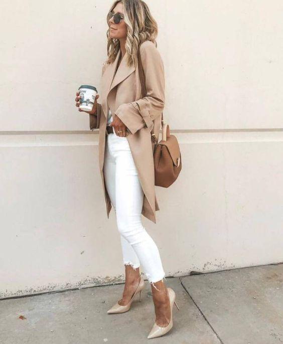 Белые джинсы скинни, бежевый тренч и нюдовые лаковые лодочки на невысоком каблуке. Образ дополнен коричневой поясной сумкой и очками.
