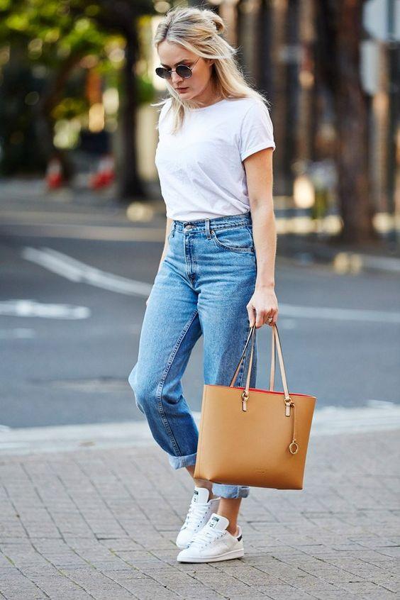 Повседневный образ - прямые светлые джинсы, простая белая футболка и кроссовки. Образ дополнен очками и коричневой сумкой.