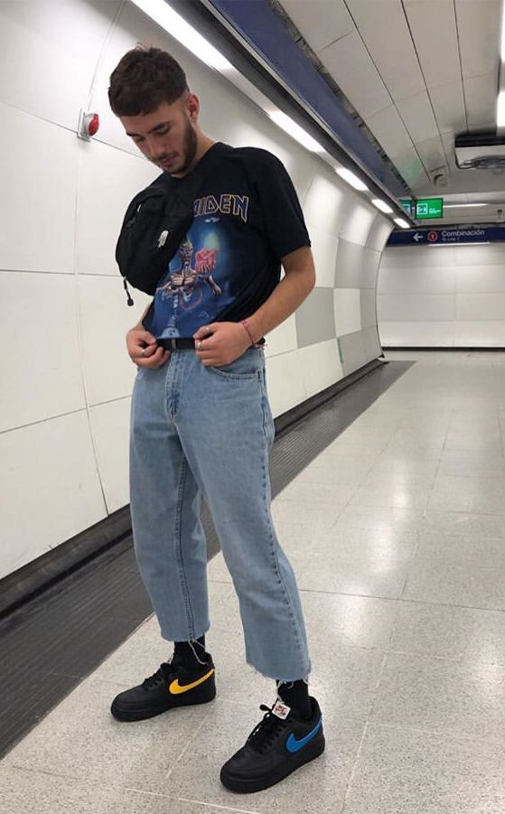 На фото широкие светлые джинсы, футболка с ярким принтом и черные кроссовки.