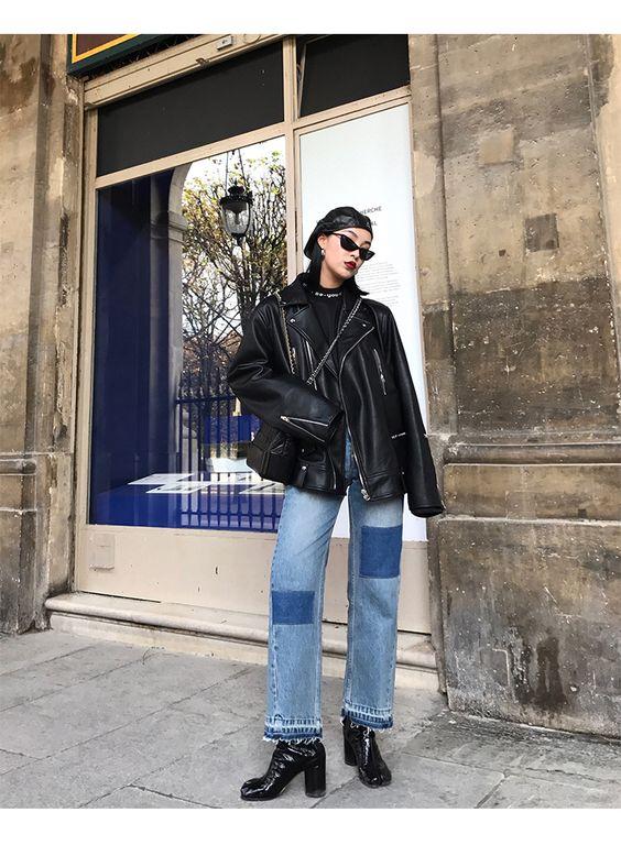 Голубые джинсы с заплатами, черная кожаная куртка oversize и лаковые ботинки на толстом каблуке. Образ дополнен беретом и очками.