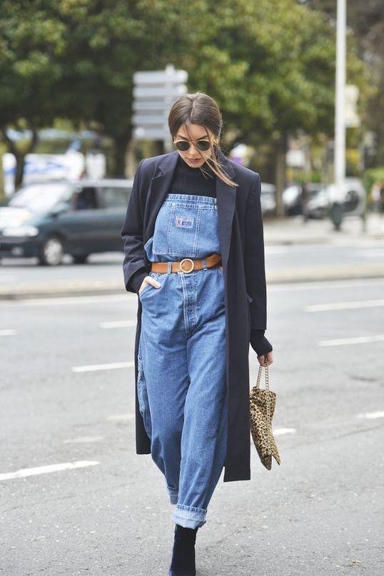 Синий джинсовый комбинезон, подчеркнутый коричневым ремнем, длинное прямое черное пальто, замшевые ботинки на каблуке и леопардовая сумка.
