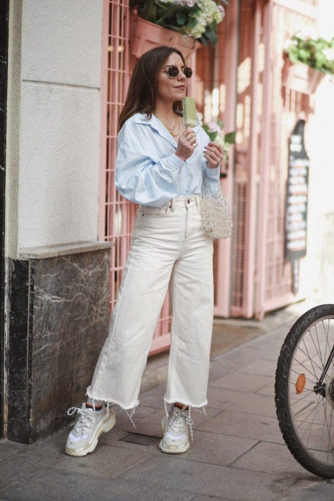 Белые джинсы клеш, голубая объемная рубашка и белые массивные кроссовки хорошо сочетаются вместе.
