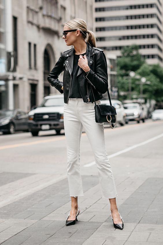 На девушке черный топ и кожаная куртка, белые прямые джинсы и черные туфли на невысоком каблуке, черная поясная сумка и очки.