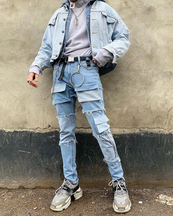 На фото голубые джинсы с карманами, такого же цвета куртка и серые массивные кроссовки.