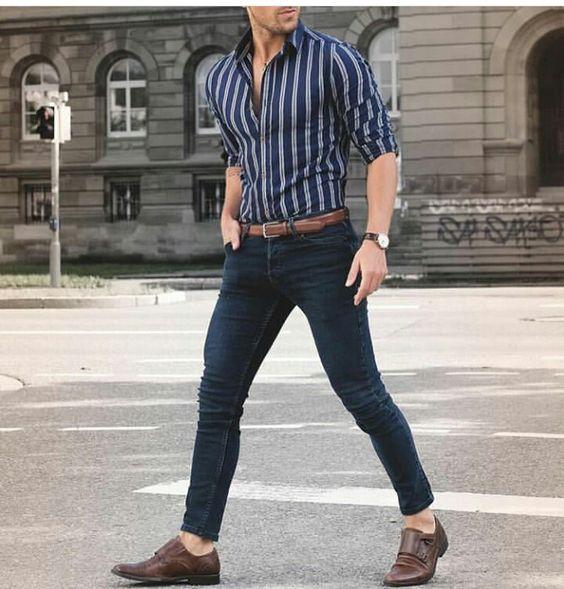 Облегающая рубашка в полоску, темно-синие джинсы скинни, коричневые туфли и ремень в тон к ним.