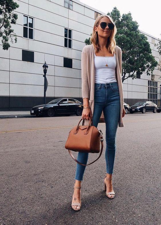 На фото облегающие джинсы,белая майка и нюдовая удлиненная кофта подходят под замшевые бежевые босоножки на толстом каблуке.