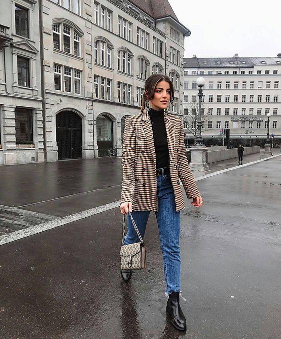 На девушке темно-синие укороченные джинсы бойфренд, черный гольф,  клетчатый удлиненный пиджак и кожаные ботинки челси.