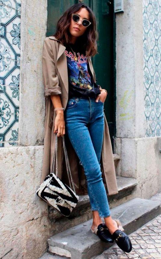 На девушке синие джинсы скинни, черные мюли, футболка с ярким принтом и нюдовый тренч. Лук дополнен очками и поясной черно-белой сумкой.