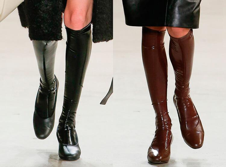 Лаковые сапоги-чулки подчеркивают стройные ноги.
