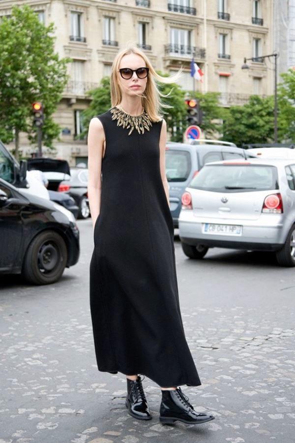 Черные лаковые полусапожки и длинное платье свободного кроя умело дополнены аксессуарами в виде ожерелья и солнцезащитных очков.