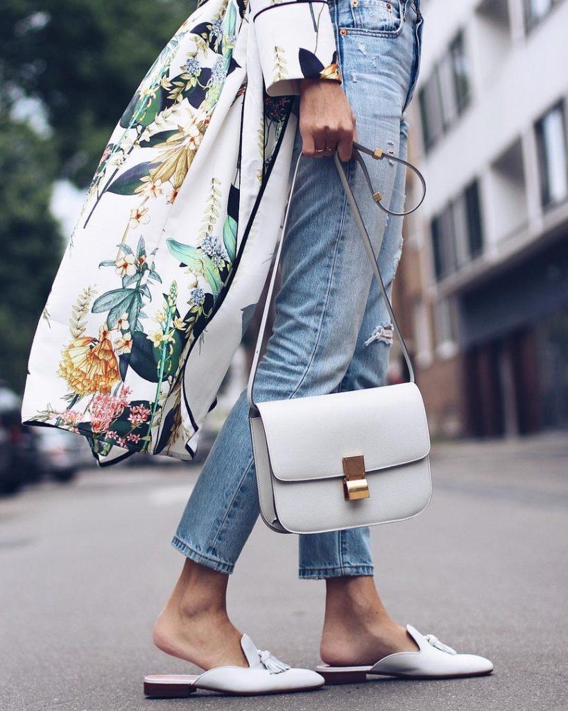 Светлые мюли с кисточками, джинсы, тренч с цветочным принтом и белая сумка — приятный освежающий аутфит.