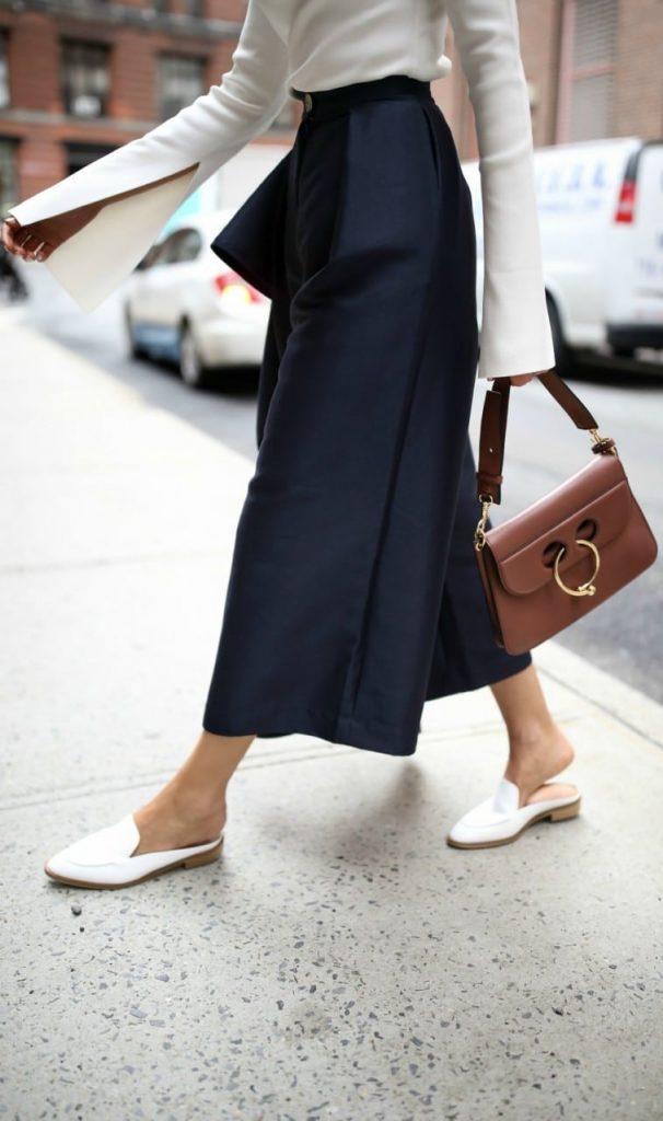 Белые мюли с кюлотами, светлой кофтой и небольшой рыжей сумкой смотрятся богато.