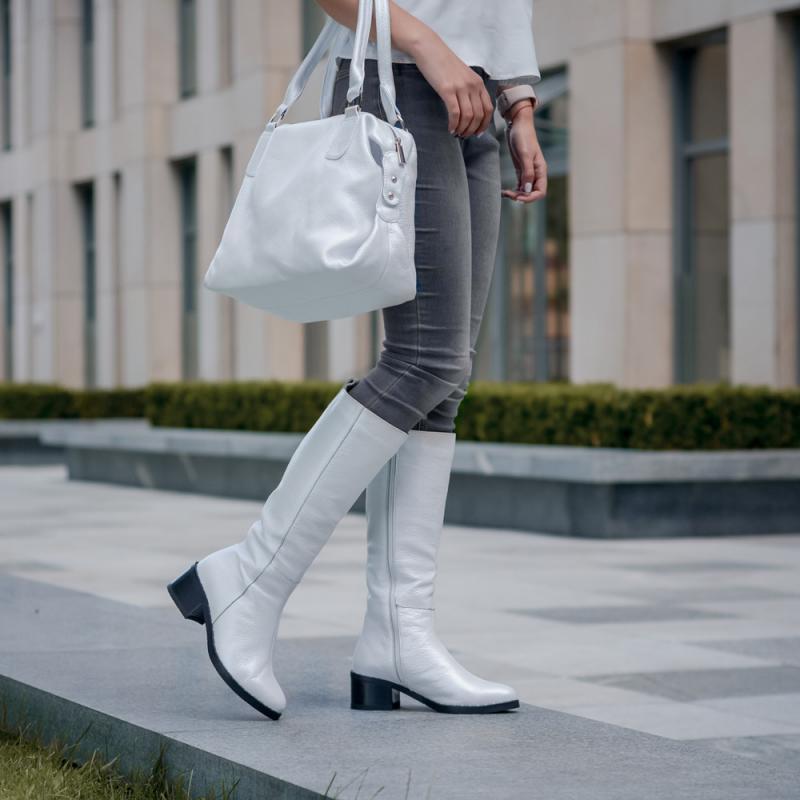 Светлые сапоги до колена с кофтой такого же оттенка, серыми брюками и белой сумкой смотрятся нарядно.