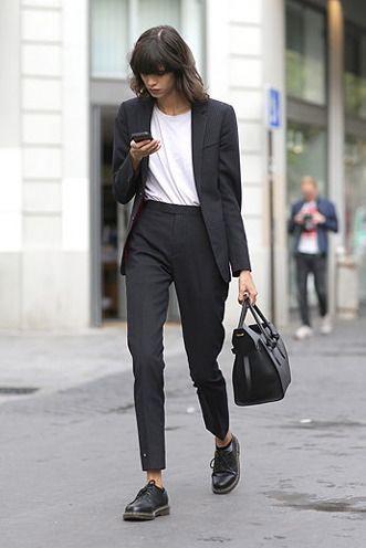 На девушке классический черный брючный костюм, белая футболка и черные кожаные броги.