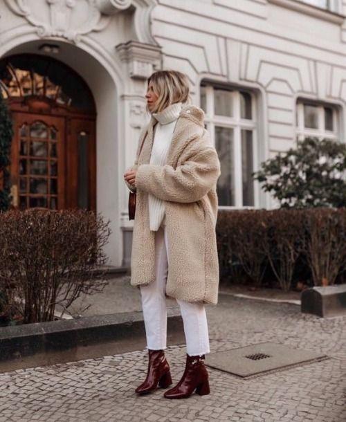 На девушке бежевая искусственная шуба, вязаный свитер oversize, белые прямые джинсы длины ⅞ и кожаные темно-коричневые полуботинки на невысоком, расширенном к низу каблуке и острым носом.