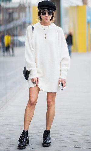 На девушке белое платье-свитер oversize и черные лаковые полуботинки на шнуровке. Образ дополняет черный берет, очки и рюкзак.