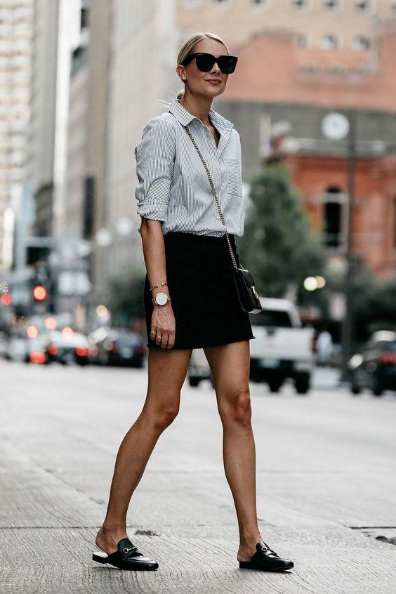 На девушке рубашка в полоску, черная мини-юбка и кожаные мюли с декором в виде цепочки на низком ходу. Образ дополнен черной поясной сумкой, очками, аксессуарами.