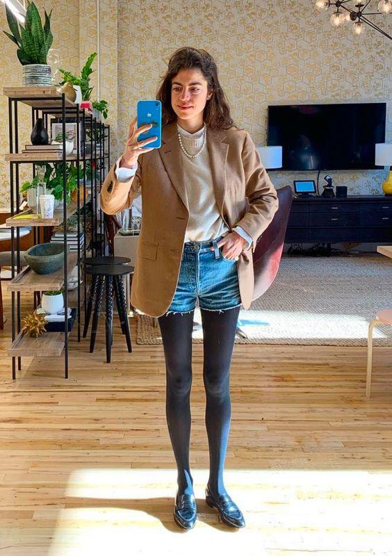 Белый свитер,коричневый пиджак свободного кроя, джинсовые шорты, черные колготы в сочетании с черными лаковыми лоферами.