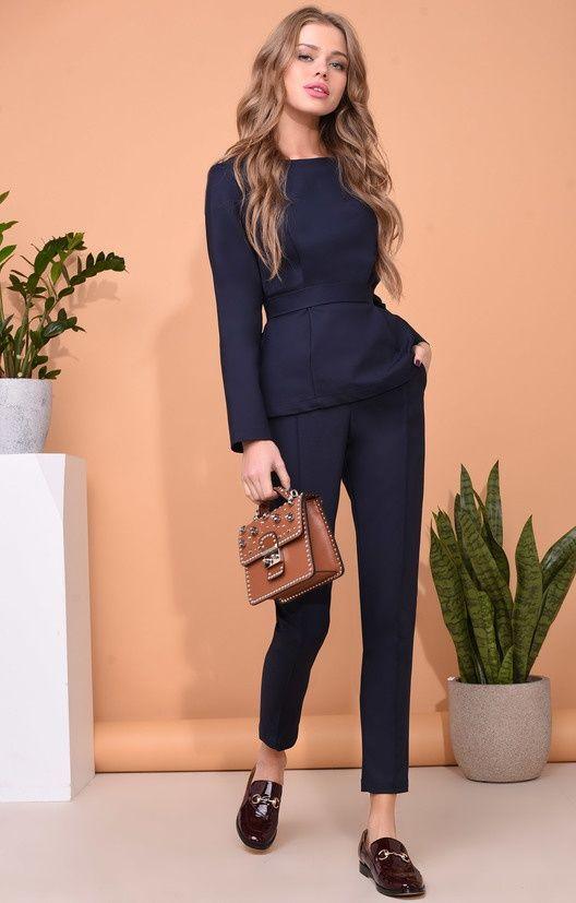 На девушке синий брючный костюм и коричневые лаковые лоферы на маленьком каблуке.