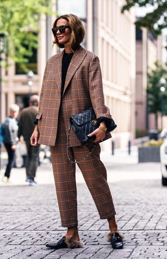 Стильный клетчатый костюм в сочетании с черными кожаными мюлями с декором в виде меха и цепочки. Образ дополнен очками и черной кожаной сумкой.