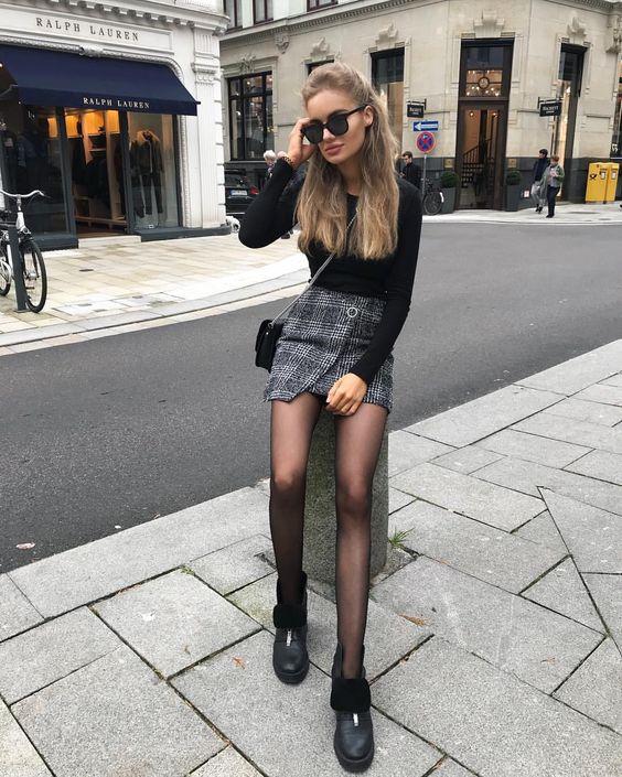 На девушке черная водолазка, серая мини-юбка, колготки и черные полуботинки на плоской подошве.