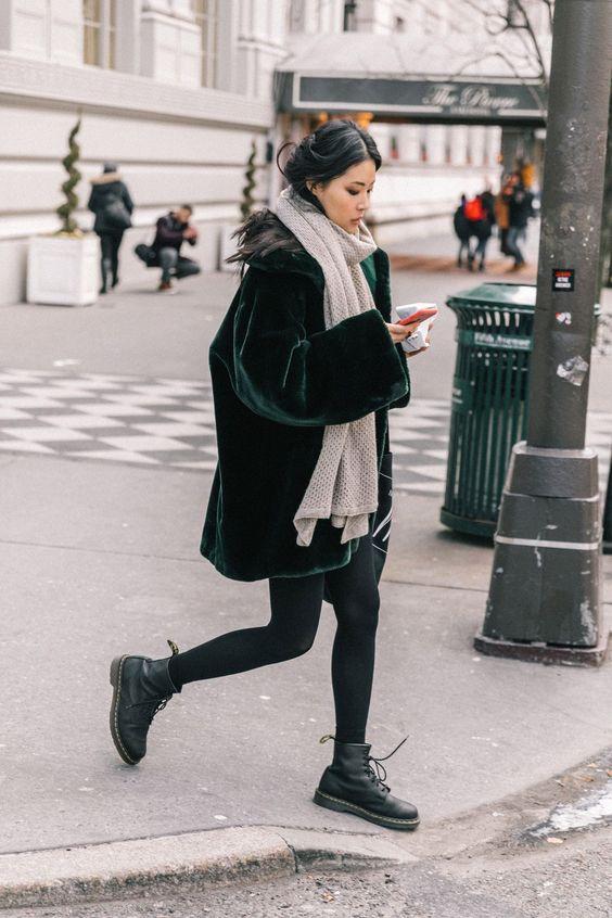 Искусственная темно-зеленая шуба выше колена, бежевый шарф, теплые колготки в сочетании с грубыми черными кожаными ботинками на шнуровке.