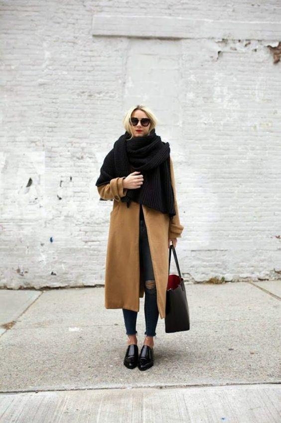 Бежевое замшевое пальто свободного кроя, синие джинсы скинни отлично сочетаются с лаковыми полуботинками без каблука с заостренным носком. Образ дополнен объемным черным шарфом, большой кожаной сумкой и очками.
