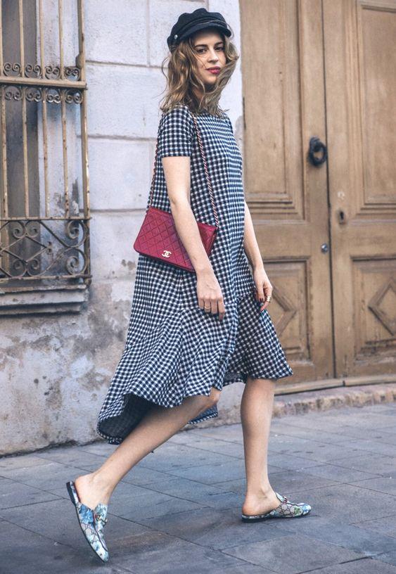 Клетчатое свободное платье миди в сочетании с мюлями на низком ходу анималистического принта. Образ дополнен красной поясной сумкой.