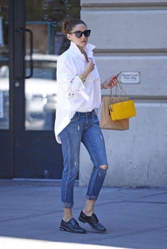 На девушке белая рубашка oversize, темно-синие джинсы с потертостями и черные полуботинки. Образ дополняют аксессуары, очки и желтая сумка.