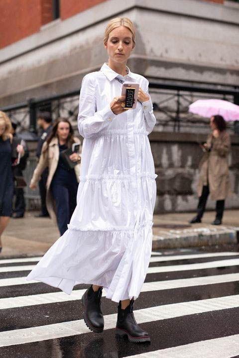 Белое платье миди с воланами в сочетании с грубыми кожаными черными ботинками.