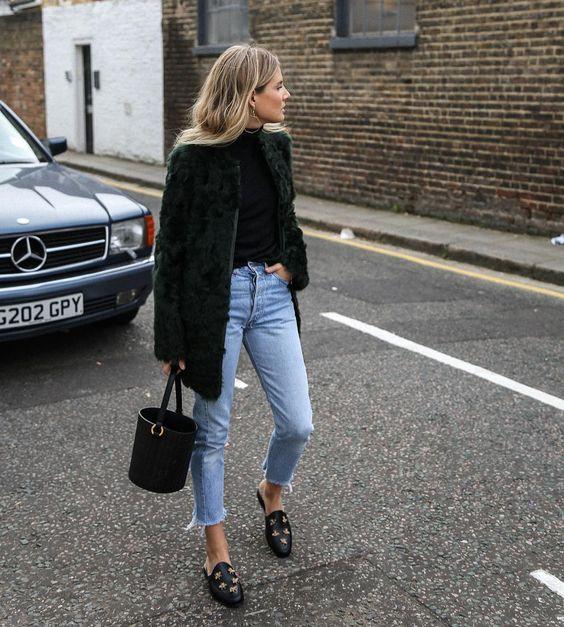 На девушке черная водолазка, искусственная шуба, прямые укороченные джинсы и кожаные мюли.