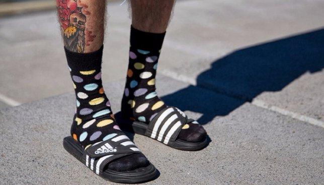 Черные носки с разноцветными кругами в сочетании с черно-белыми мужскими сандалиями.