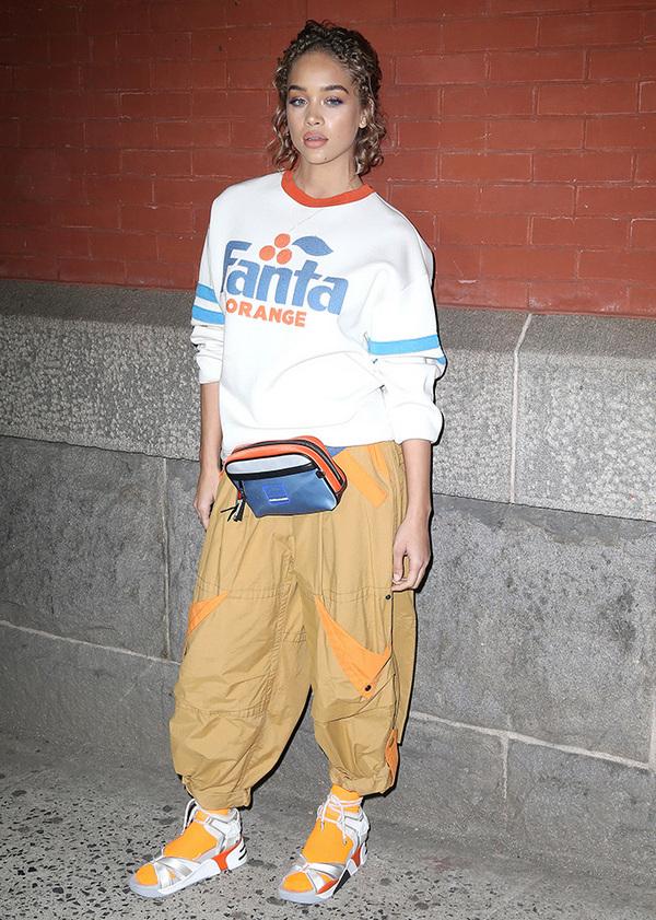 На девушке белый свитшот, коричневые спортивные брюки, яркие оранжевые носки и белые спортивные сандалии на танкетке.