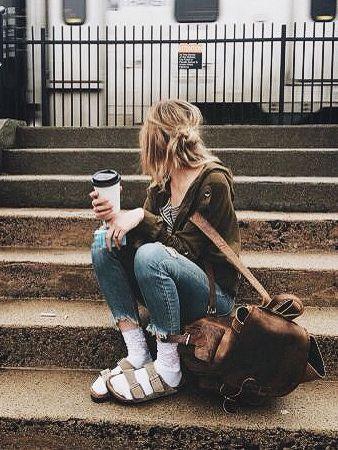 На девушке темно-зеленая куртка, синие джинсы, бежевые сандалии и высокие белые носки.