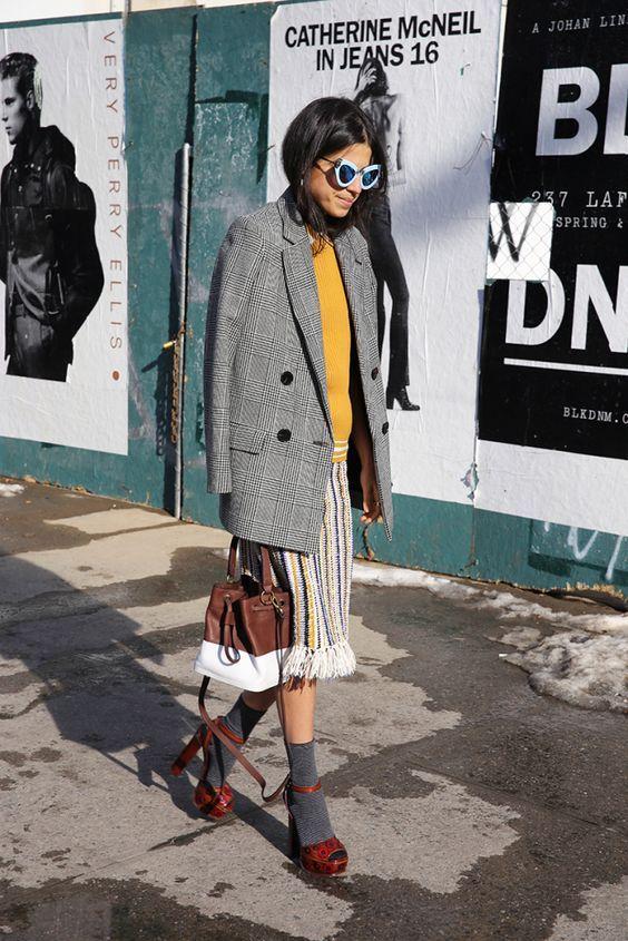 На девушке серый клетчатый пиджак, юбка ниже колена, серые высокие носки и коричневые босоножки на платформе и высоком каблуке.